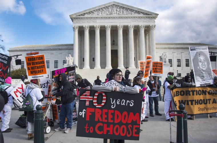 Pro-choice activists hold up placards in front of the US Supreme Court in Washington, DC, January 22, 2015, as they await the pro-choice activist with the March For Life. (JIM WATSON/AFP/Getty Images)
