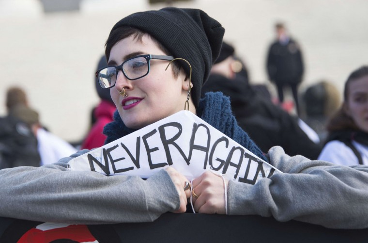 "Pro-choice activists holds a coat hanger, historically used for self-induced abortion, that reads ""never again"" in front of the US Supreme Court in Washington, DC, January 22, 2015, as they await the pro-choice activist with the March For Life. (JIM WATSON/AFP/Getty Images)"
