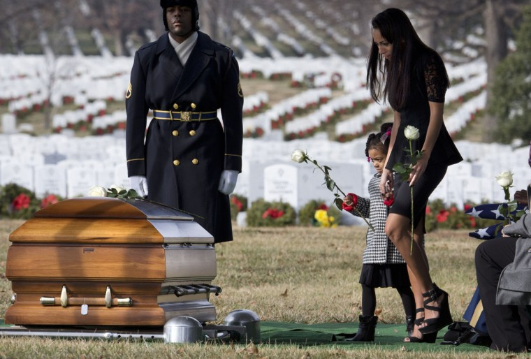 Ariana Morris, 3, walks with her mother Christina Strange to lay a white rose on the casket of her father, Army Sgt. 1st Class Ramon S. Morris, of New York City, during burial services at Arlington National Cemetery in Arlington, Va., Friday, Jan. 23, 2015. According to the Defense Department, Morris died Dec. 12, 2014, in Parwan Province, Afghanistan, of wounds suffered when the enemy attacked his vehicle with an improvised explosive device. (AP Photo/Jacquelyn Martin)