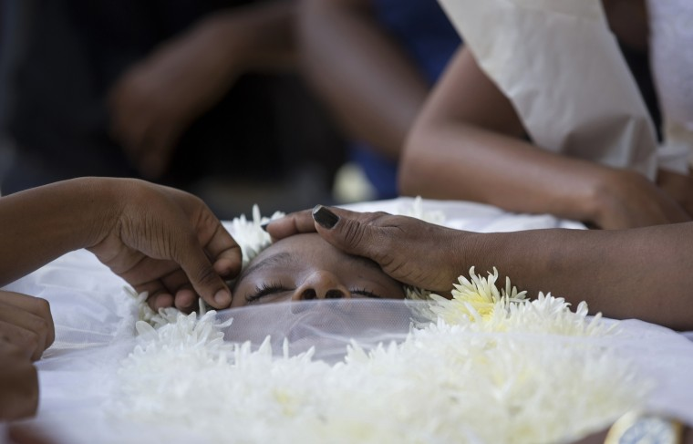 In this Jan. 27 photo, relatives and friends touch the face of Adriene Nascimento who was killed by a stray bullet, during her funeral at the Sao Joao Batista cemetery in Rio de Janeiro, Brazil. Nascimento, a 21-year-old mother of two, died holding a child in her lap when a stray bullet came as police and gang members traded fire nearby. (AP Photo/Silvia Izquierdo)