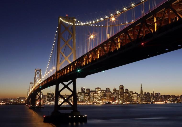The San Francisco-Oakland Bay Bridge towers over the city skyline at dusk on Wednesday, Jan. 7, 2015, in San Francisco. (AP Photo/Marcio Jose Sanchez)