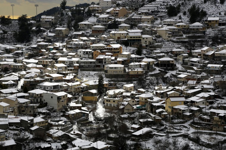 Snow cover the roofs of the houses seen at Kyperounta village after four-days heavy snowing on Troodos mountain, Cyprus, Thursday, Jan. 8, 2015. Cyprus is in the grip of a mid-winter storm bringing heavy rains, low temperatures and snow in the Troodos mountain range. (AP Photo/Petros Karadjias)