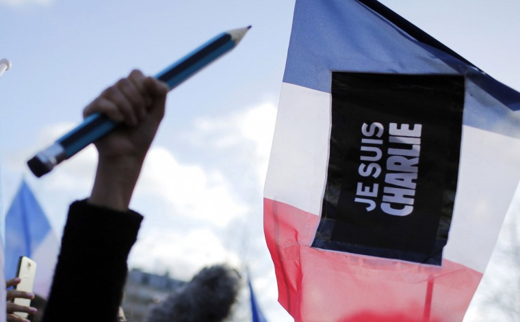 A demonstrator holds up an oversized pencil at Republique Square, Paris, before the start of a demonstration, Sunday, Jan. 11, 2015. A rally of defiance and sorrow, protected by an unparalleled level of security, on Sunday will honor the 17 victims of three days of bloodshed in Paris that left France on alert for more violence. (AP Photo/Laurent Cipriani)