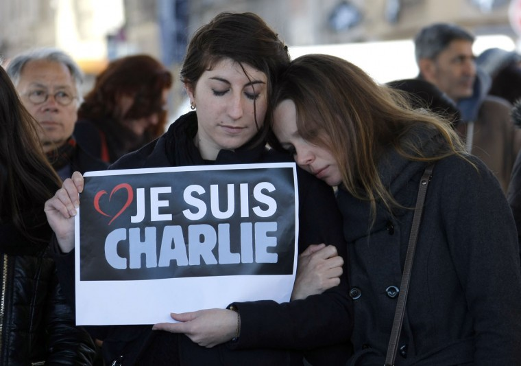 """People pay tribute to the victims of the satirical newspaper """"Charlie Hebdo"""", in Marseille, southern France, Thursday, Jan. 8, 2015, a day after masked gunmen stormed the offices of a satirical newspaper and killed 12 people. French police hunted Thursday for two heavily armed men ó one with a terrorism conviction and a history in jihadi networks ó in the methodical killing of 12 people at a satirical newspaper that caricatured the Prophet Muhammad. Placard reads """"I am Charlie"""". (AP Photo/Claude Paris)"""