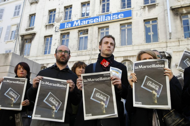 """Employees and journalists of the newspaper """"La Marseillaise"""" hold a journal of the day, reading"""" I am Charlie"""" , in front of the newspaper building during a minute of silence , in Marseille, southern France, Thursday, Jan. 8, 2015, a day after masked gunmen stormed the offices of a satirical newspaper and killed 12 people. French police hunted Thursday for two heavily armed men ó one with a terrorism conviction and a history in jihadi networks ó in the methodical killing of 12 people at a satirical newspaper that caricatured the Prophet Muhammad. The prime minister announced several overnight arrests and said the possibility of a new attack """"is our main concern."""" (AP Photo/Claude Paris)"""