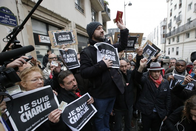 """Journalist hold up their press cards during a minute of silence outside the Charlie Hebdo newspaper in Paris, Thursday, Jan. 8, 2015, a day after masked gunmen stormed the offices of a satirical newspaper and killed 12 people. Protesters in some U.S. cities ó repeating the viral online slogan """"Je Suis Charlie"""" or """"I Am Charlie"""" demonstrated against the deadly terror attack on a Paris newspaper office, joining thousands around the world who took to the streets to rally against the killings. (AP Photo/Francois Mori)"""