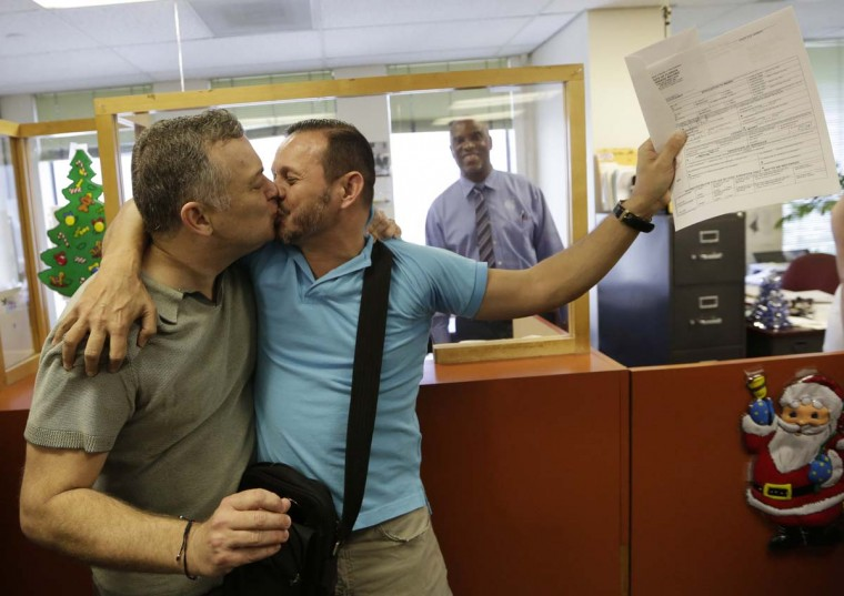 Jeff Ronci, 53, left, kisses his partner of 15 years, Juan Talavera, 46, as they hold up their marriage license at the Miami-Dade County Clerk of Courts office, Monday, Jan. 5, 2015, in Miami. A circuit judge judge lifted a stay on her July ruling that Florida's same sex marriage ban violates equal protections under the U.S. Constitution. The first gay and lesbian weddings could take place as early as Monday. (AP Photo/Lynne Sladky)