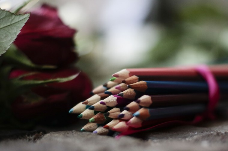Colored pencils and flowers to commemorate the victims killed in an attack at the Paris offices of the weekly newspaper Charlie Hebdo, sit in front of the French Embassy in Berlin, Thursday, Jan. 8, 2015. Masked gunmen stormed the Paris offices of a weekly newspaper that caricatured the Prophet Muhammad, methodically killing 12 people Wednesday, including the editor, before escaping in a car. It was France's deadliest postwar terrorist attack.(AP Photo/Markus Schreiber)