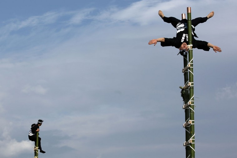 Members of a traditional firefighting preservation group perform ladder stunts during the annual New Year's Fire Brigade Review in Tokyo, Tuesday, Jan. 6, 2015. (AP Photo/Eugene Hoshiko)