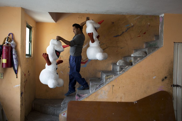 "In this Jan. 23 photo, Guillermo Luna Martinez, 36, carries freshly painted piñatas representing Disney's Frozen snowman character Olaf downstairs to where his wife Elvia Vicente Albarran will use paper to craft the character's eyes, teeth, and distinctive tuft of hair, at the family's workshop in the Iztapalapa neighborhood of Mexico City. Though Luna and his wife have chosen to work in the family business, they plan to let their children, Guillermo, 10, and Melissa, 9, decide for themselves. ""Who knows if the business will last forever,"" said Luna, ""I'd prefer that they study and get a career, for them to have a better future."" (AP Photo/Rebecca Blackwell)"