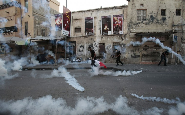 Bahraini anti-government protesters clash with riot police firing tear gas during clashes in Bilad Al Qadeem, Bahrain, a suburb of Manama, Tuesday, Jan. 6, 2015. Escalated clashes have continued for more than a week because of the detention of Bahraini Shiite opposition leader Sheik Ali Salman. (AP Photo/Hasan Jamali)