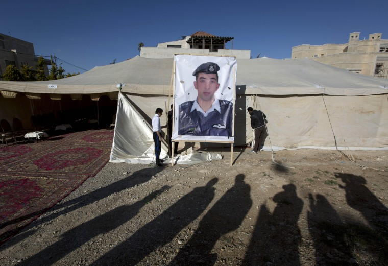A banner with a picture of Jordanian pilot, Lt. Muath al-Kaseasbeh, who is held by the Islamic State group militants, is being raised by workers near a tent prepared for receiving supporters, in Amman, Jordan, Friday, Jan. 30. The fates of a Japanese journalist and Jordanian military pilot were unknown Friday, a day after the latest purported deadline for a possible prisoner swap passed with no further word from the Islamic State group holding them captive. (AP Photo/Nasser Nasser)