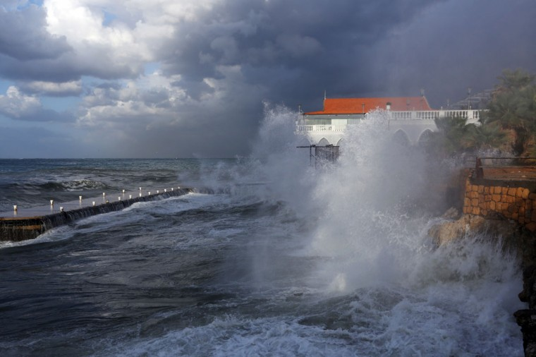 Huge waves crash on the sea defense wall of a restaurant, at the Beirut corniche, Lebanon, Tuesday, Jan. 6, 2015. Lebanon is under the effects of a blustery storm, dropped torrential rain and snow and pushed temperatures below freezing in northern Lebanon and some areas of the Bekaa Valley, which is dotted with informal Syrian refugee settlements. (AP Photo/Bilal Hussein)