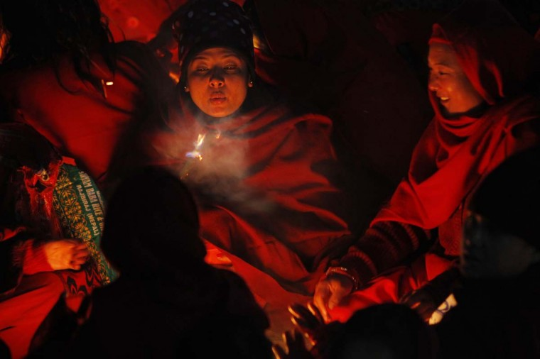 Nepalese women devotees sit around a bonfire to warm themselves before they take holy deep in Salinadi River during the first day of month long Swasthani Bratakatha festiva in Sankhu, on the outskirts of Katmandu, Monday, Jan. 5, 2015. During this month-long festival, devotees recite Holy Scriptures dedicated to Hindu goddess Swasthani and Lord Shiva. Unmarried women pray to have a good husband while those married pray for the longevity of their husbands by observing a month-long fast. (AP Photo/Niranjan Shrestha)
