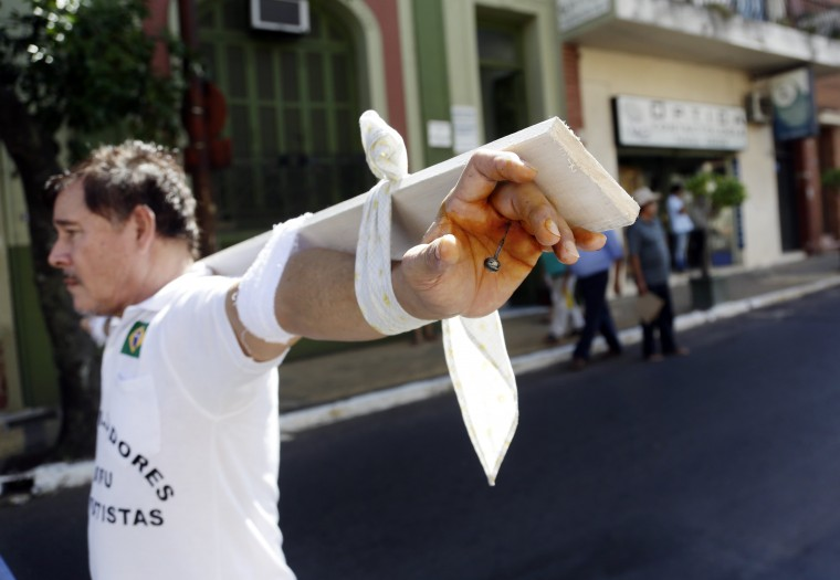 Roberto Gonzalez, a former worker of Unicom and Conempa, Paraguayan Itaipu Dam contractors, walks in the streets of Asuncion towards the Ministry of labor, in a symbolic crucifixion, in Paraguay, Monday, Jan. 26, 2015. Gonzalez is part of a group that for the last 25 years, after the construction on the dam was completed, is demanding compensation benefits from the contractors. The Itaipu hydroelectric dam on the Parana River straddles the Brazil-Paraguay border. (AP Photo/Jorge Saenz)