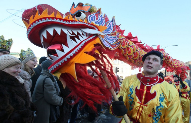 A dragon is carried during the traditional Roman Catholic Epiphany procession in the streets of Warsaw, Poland, Tuesday, Jan. 6, 2015. (AP Photo/Czarek Sokolowski)