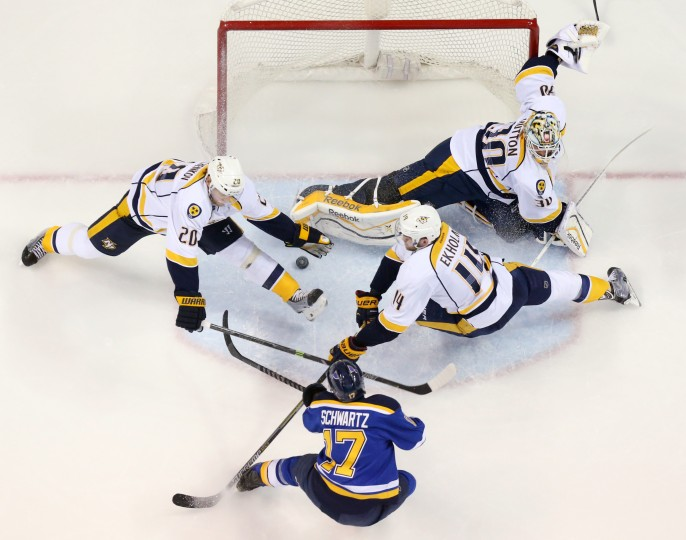 St. Louis Blues left wing Jaden Schwartz threads the puck between two defenders and past Nashville Predators goaltender Carter Hutton to score during the second period of an NHL hockey game Thursday, Jan. 29, in St. Louis. (AP Photo/St. Louis Post-Dispatch, Chris Lee)