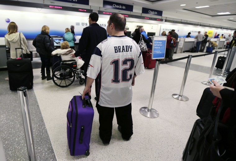 New England Patriots fan Anthony Monaco, of the South Boston neighborhood of Boston, waits in line for his flight to Phoenix, at Logan Airport in Boston, Monday, Jan. 26, 2015. Monaco, who has Super Bowl tickets, hopes to fly out of the Boston before a winter storm that is expected to hit the area with about two feet of snow in the winter storm. (AP Photo/Charles Krupa)