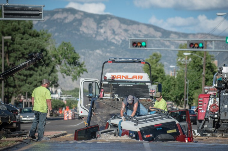 In this Saturday, July 18, 2015 photo, men work to pull Lynn Parsons' SUV out of a sinkhole caused by a water main break on eastbound Indian School Road near American's Parkway in Albuquerque, N.M. Parsons, of East Mountain, was on her way to buy groceries when the pavement underneath gave way and her SUV sank into the street up to the driver's side window with water spraying everywhere. (Roberto E. Rosales/The Albuquerque Journal)