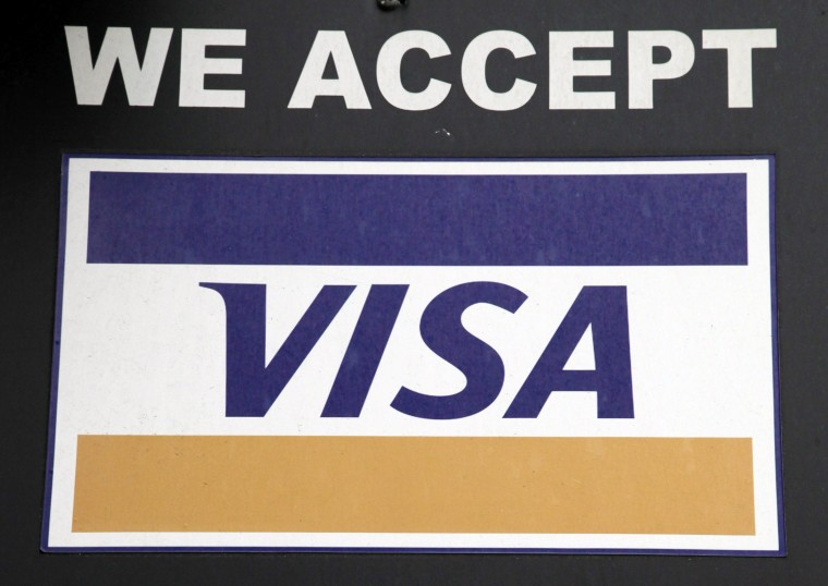 In this Jan. 21 photo, a sign indicating Visa credit cards are accepted is posted at a New York business. Visa's quarterly profit rose 11 percent as consumer spending grew on the credit and debit card processor's massive payment network, the company announced Thursday, Jan. 29, 2015. (AP Photo/Mark Lennihan)