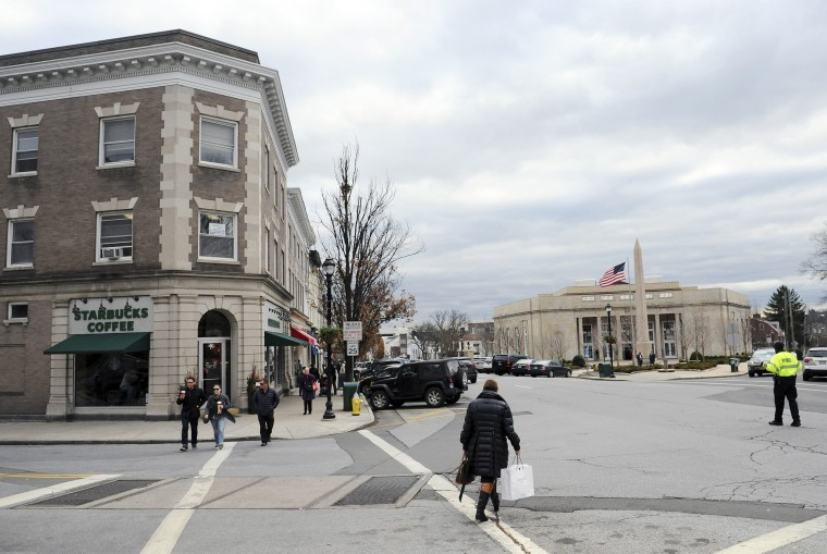 In this Dec. 17, 2014 photo, people cross the street at the intersection of Greenwich Avenue and Havemeyer Place in downtown Greenwich, Conn. The nation's political center cuts directly between super-wealthy Greenwich and high-achieving Chappaqua, N.Y. Separated by just 13 miles, these sought-after suburbs lay claim to the two most powerful political families of the 21st century: the Bushes and the Clintons. (AP Photo/Hearst Connecticut Media/Greenwich Time, Tyler Sizemore)