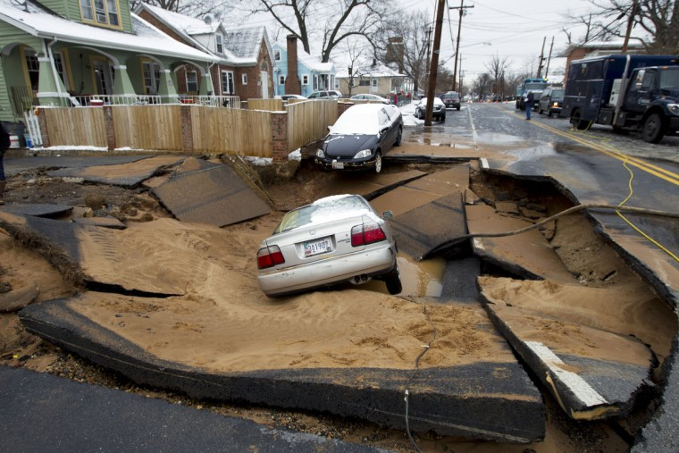 Cars swallowed by a sinkhole that occurred after a water main break in Bladensburg, Md., Tuesday, Jan. 27, 2015. A water main break caused a sinkhole in a suburban Washington, D.C. neighborhood, swallowing up a family's car just after they escaped in Bladensburg Maryland on Tuesday morning. (Jose Luis Magana/AP Photo)