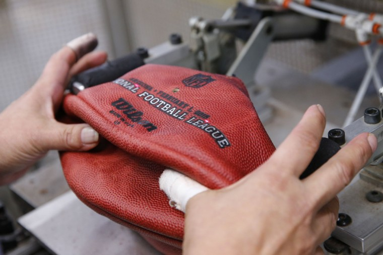 An official game ball for NFL football's Super Bowl XLIX is lined up to have the team names' stamped on it at the Wilson Sporting Goods Co. in Ada, Ohio, Tuesday, Jan. 20, 2015. The New England Patriots face the Seattle Seahawks for the NFL championship on Sunday, Feb. 1, 2015, in Glendale, Ariz. (AP Photo/Rick Osentoski)