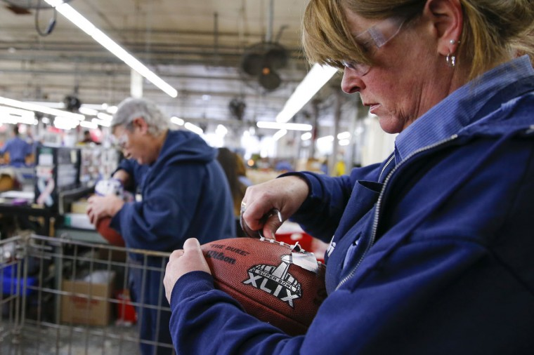 Barb Harnishfeger inspects an official game ball for NFL football's Super Bowl XLIX before it is shipped out at the Wilson Sporting Goods Co. in Ada, Ohio, Tuesday, Jan. 20, 2015. The New England Patriots face the Seattle Seahawks for the NFL championship on Sunday, Feb. 1, 2015, in Glendale, Ariz. (AP Photo/Rick Osentoski)