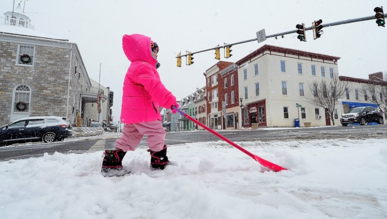 Paiden Beasley, 4, helps her step-brother shovel snow along Conococheague Street in Williamsport, Md., Tuesday, Jan. 6, 2015. (AP Photo/The Herald-Mail, Ric Dugan)