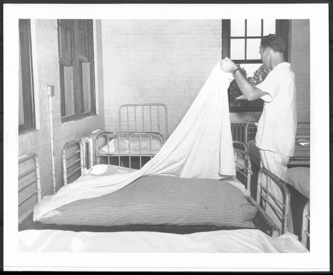 An attendant making a bed of straw and hay at Crownsville State Hospital.