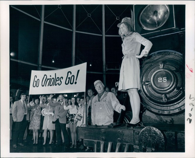 "American League Championship 1973: Susie Palmer, wife of Oriole hurler Jim Palmer, leads Chessie System (Chesapeake & Ohio and Baltimore & Ohio railroad) employees in a cheer for the Birds. Mrs. Palmer is standing on the William Mason locomotive in the B&O Transportation Museum. The play-offs begin at Memorial Stadium Saturday. The crowd holds the banner ""Go Orioles Go!"""