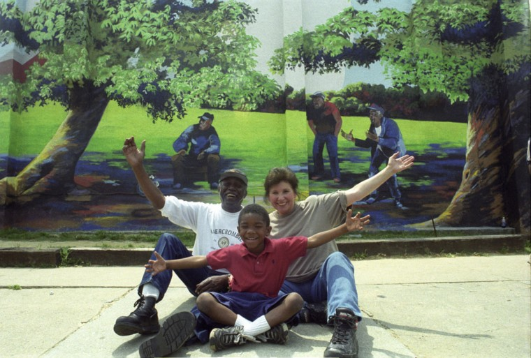 """July 6, 1999: Larger than life. To show the scale of her work, Mary Carfagno Ferguson stands next to her mural """"Horseshoe Players,"""" at the northeast corner of Bayard and Ward streets in the Carrolltown neighborhood of Pigtown. Baltimore Sun file photo"""