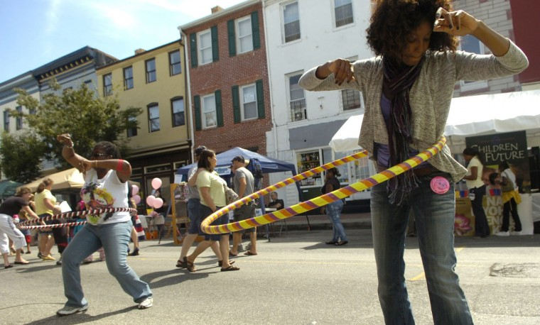 9/11/10: Anjelica Hebern, right, and Hazel Alexander, both with the Buddhist group Soka Gakkai International, perform with hula hoops during the Pigtown Festival. Photo by Brian Krista/Baltimore Sun