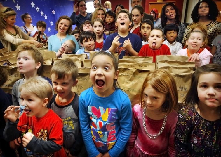 Young volunteers with the Little Helpers make their best 'funny faces' while posing with nearly 1,000 bagged bologna sandwiches they made at Neshoba Unitarian Universalist Church Sunday, January 18, 2015 in Memphis, Tenn. to be passed out at the First Presbyterian Soup Kitchen. The monthly service project is an important part of the Little Helpers mission to help kids understand the value of volunteering. (AP Photo/The Commercial Appeal, Jim Weber)