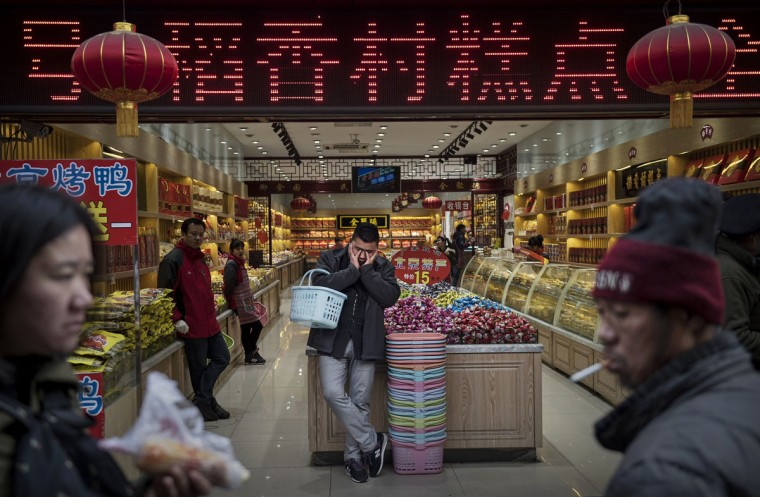 A Chinese customer rests as he stands in a store in a shopping district on January 20, 2014 in central Beijing, China. China's economic growth slowed to its weakest point in years to 7.4 percent. While its growth is stronger than most world economies, China announced Tuesday a strategy to encourage domestic consumption including retail spending in an effort to boost growth. (Kevin Frayer/Getty Images)