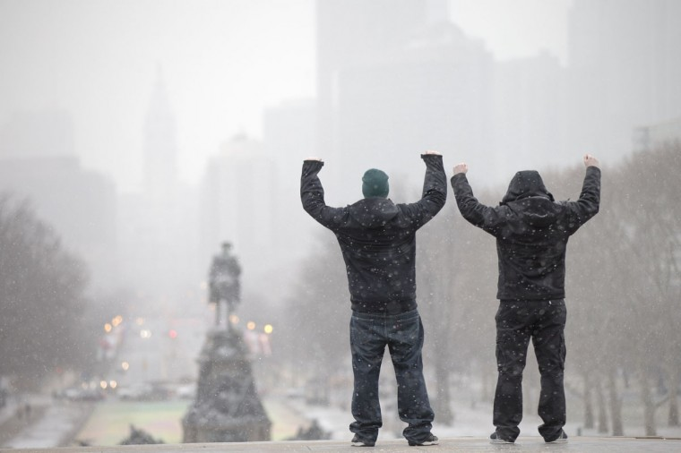 """During a winter storm tourists imitate the character Rocky Balboa from the 1976 movie """"Rocky,"""" on the steps of the Philadelphia Museum of Art, Wednesday, Jan. 21, 2015, in Philadelphia. (AP Photo/Matt Rourke)"""