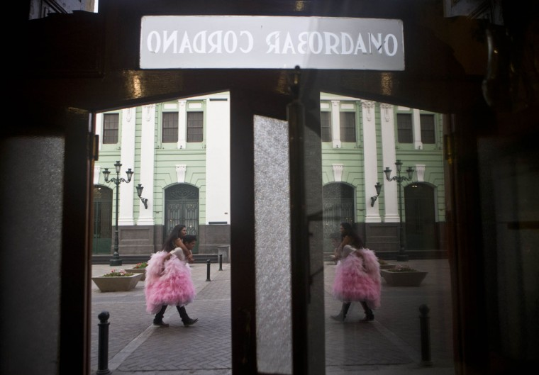 """Daysi Villavicencio rides on the back of a photographer's assistant to keep her gown from getting dirty as they're reflected in a mirror at the iconic Cordano Bar in Lima, Peru, Thursday, Jan. 22, 2015. Villavicencio is celebrating her 15th birthday and had a series of pictures made in her formal """"quinceanera"""" gown. (AP Photo/Esteban Felix)"""