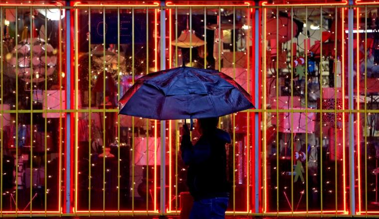 A pedestrian walks past Light Bulbs Unlimited during a recent rain shower along Westheimer Road, Thursday, Jan. 22, 2015, in Houston. (AP Photo/Houston Chronicle, Gary Coronado)