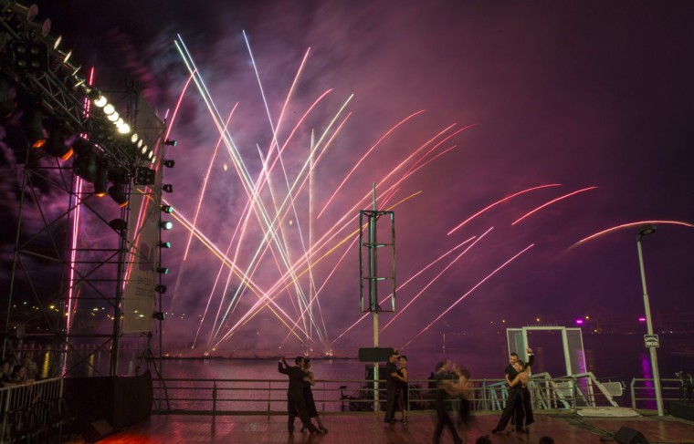 """Couples dance tango as fireworks go off in La Boca neighborhood of Buenos Aires, Argentina, late Saturday, Jan. 24, 2015. The performance, coined """"La vida es una milonga,"""" or Life is a Milonga, was organized by artist Cai Guo-Qiang. (AP Photo/Ivan Fernandez)"""