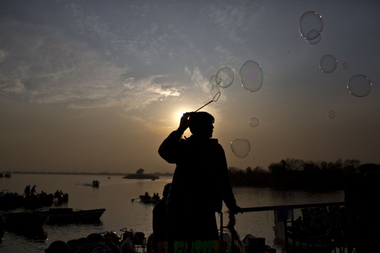 A Pakistani vendor releases bubbles to attract customers visiting Lake View park in Islamabad, Pakistan, Saturday, Jan. 24, 2015. (AP Photo/Muhammed Muheisen)