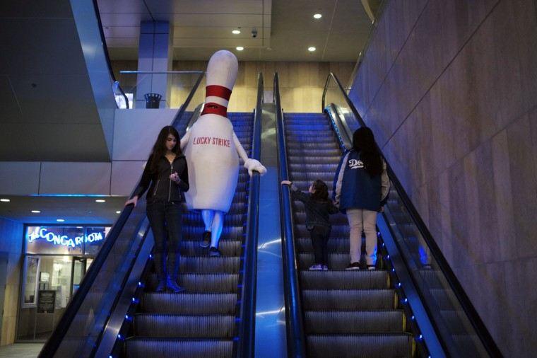A person dressed as a bowling pin rides an escalator on Tuesday, Jan. 27, 2015, in Los Angeles. (AP Photo/Jae C. Hong)