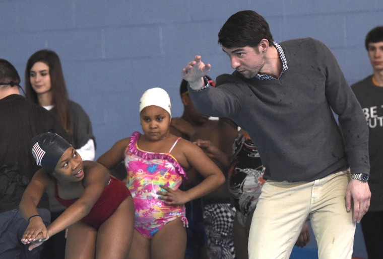 """Olympic swimmer Michael Phelps, right, instructs Shakayla Blair, left, during swim team practice at the Haslam Family Club University, Wednesday, Jan. 28, 2015, in Knoxville, Tenn. Phelps coached the swim team on behalf of the Boys & Girls Clubs of the Tennessee Valley and participated in an announcement about the """"Our Kids, Our Future"""" campaign. (AP Photo/Knoxville News Sentinel, Adam Lau)"""
