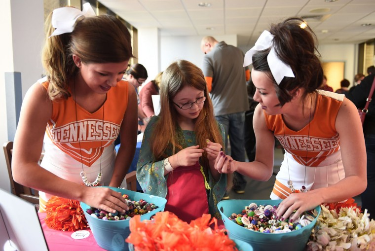 University of Tennessee cheerleaders Delaney Burton, left, and Kylee Dick help patient Emilie Gregg choose beads during the Beads of Courage program at East Tennessee Children's Hospital, Wednesday, Jan. 28, 2015, in Knoxville, Tenn. The program allows children with a serious illness to record their stories of survival by collecting beads for each step of their treatment. (AP Photo/Amy Smotherman Burgess, Knoxville News Sentinel)