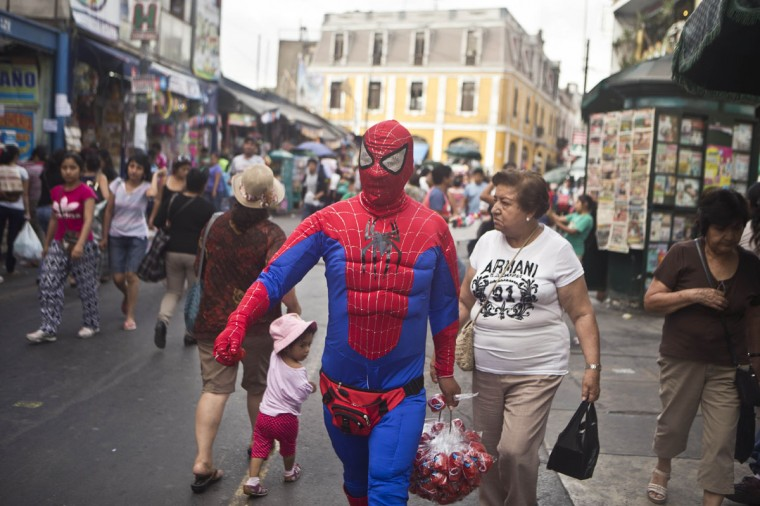 A man wearing a Spiderman costume walks outside the central market of Lima, Peru, Thursday, Jan. 29, 2015. The man disguised as a comic strip hero is a street vender who sells toys, such as rubber balls. (AP Photo/Esteban Felix)