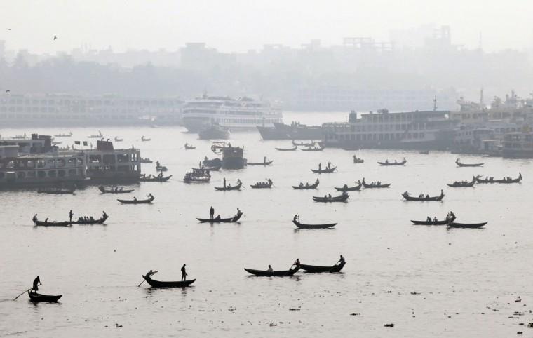 Bangladeshis on country boats cross the Buriganga River in Dhaka, Bangladesh, Thursday, Jan. 29, 2015. (AP Photo/ A.M. Ahad)