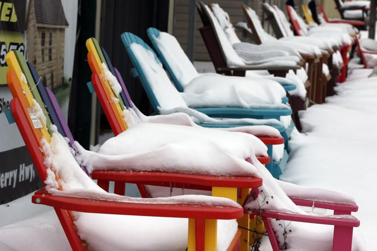 Several inches of snow from the snowstorms of the past few days cover a row of colorful outdoor chairs for sale in Zelienople, Pa. on Thursday, Jan. 29, 2015. Forecasters are predicting another clipper storm to pass through the region delivering freezing rain and snow through Friday. (AP Photo/Keith Srakocic)