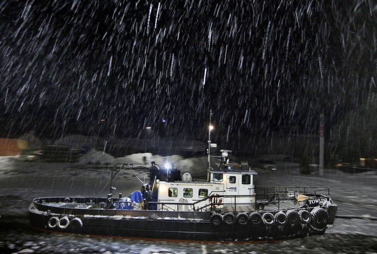 A crew member on theTowline, a 65-foot steel-hull ice breaking vessel, keeps watch while working in a snow storm to clear ice for a dredging operation on the Royal River, Friday, Jan. 30, 2015, in Yarmouth, Maine. (AP Photo/Robert F. Bukaty)