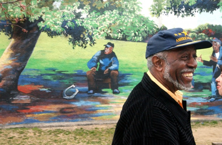 3/28/06: William Bus Chambers, known as the mayor of Pigtown, smiles as he passes a mural at the corner of Bayard and Ward Streets. Jed Kirschbaum/Baltimore Sun