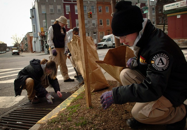 1/31/06: Alaina Hanchey, 19, of St. Joseph, MI, Isabel Leal-Rivera, of Sacramento, CA, Kristina Lentell, 20, of Denver, CO, and Natasha Dobias, 19, of Ludington, MI, clean up a corner in Pigtown. Volunteers from Americorps National Civilian Community Corps participate in a cleanup of Washington Village and Pigtown. Andre F. Chung/Baltimore Sun
