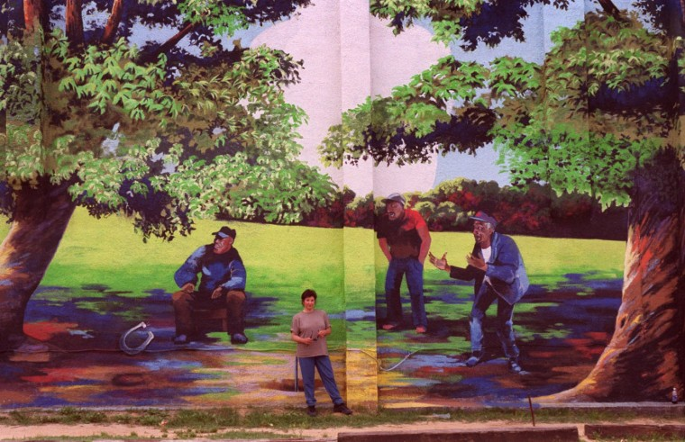 "6/25/99: To give a better idea of the scale of her work artist Mary Carfagno Ferguson, center left, stands next to her painting ""Horseshoe Players"" at the northeast corner of Bayard and Ward Sts. in the Carrolltown neighborhood of Pigtown. (Jed Kirschbaum/Baltimore Sun)"